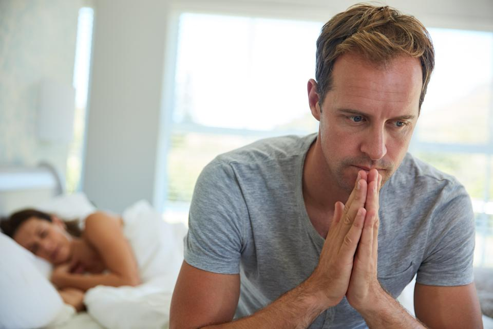 Shot of a man looking worried while his wife sleeps in the background