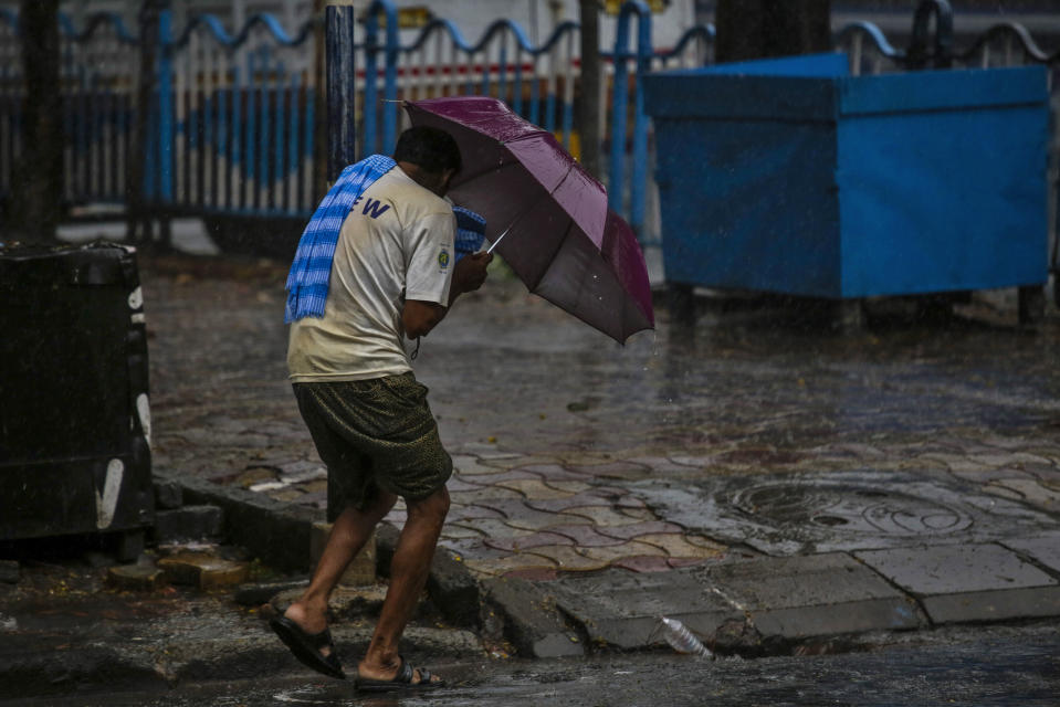 A man struggles to hold his umbrella and walk against high wind in Kolkata, India, Wednesday, May 20, 2020. Amphan, a powerful cyclone has slammed ashore along the coastline of India and Bangladesh where more than 2.6 million people fled to shelters in a frantic evacuation made all the more challenging by the coronavirus pandemic. (AP Photo/Bikas Das)