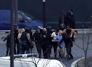 French police special forces evacuate hostages after launching an assault at a kosher grocery store in Porte de Vincennes, eastern Paris