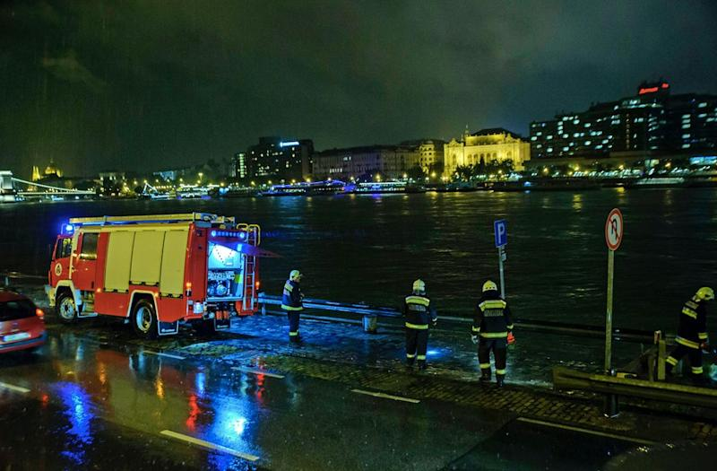 Rescuers search for victims on the river bank after a boat sank on the Danube River in Budapest (AP)