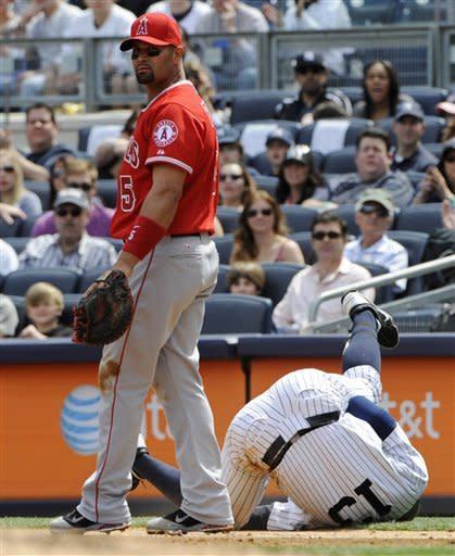 New York Yankees' Alex Rodriguez, right, is safe on a fielder's choice as  Los Angeles Angels first baseman Albert Pujols looks on during the first inning of a baseball game Saturday, April 14, 2012 at Yankee Stadium in New York. (AP Photo/Bill Kostroun)