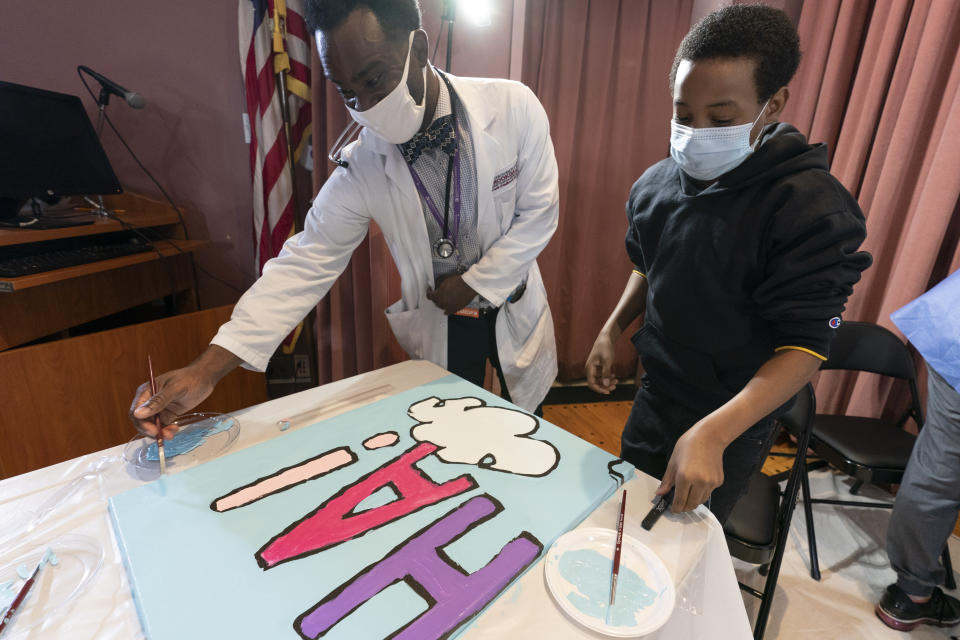 "Pediatric resident Dr. Salome Wiredu, left and Jesse McCarty, 14, paint a panel of a ""Peanuts"" mural that will be placed in the outpatient pediatric floor of One Brooklyn Health at Brookdale Hospital, Thursday, Oct. 1, 2020, in the Brooklyn borough of New York. The beloved comic marks its 70th anniversary this week with new lesson plans, a new TV show and a philanthropic push that includes donating ""Peanuts"" murals for kids to paint in 70 children's hospitals around the globe, from Brooklyn to Brazil.(AP Photo/Mary Altaffer)"