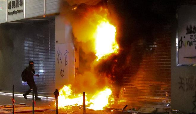 An anti-government protester starts a fire in Mong Kok. Photo: May Tse