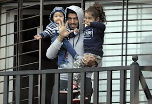 Luis Suarez holds his children as he greets fans from his home in Montevideo, Uruguay, on Friday. (AP)
