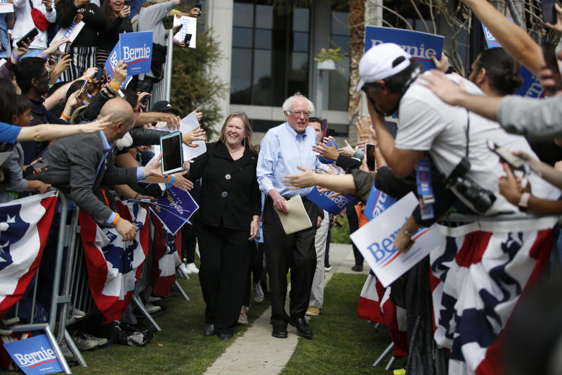 FILE - In this March 23, 2019, file photo, Democratic presidential candidate Sen. Bernie Sanders, I-Vt., center right, and his wife, Jane, arrive at a rally at Grand Park in Los Angeles. A persistent group of Sanders supporters say they won't let go of the slights from the 2016 primary fight against Hillary Clinton. The frustration is notable now that Sanders is a 2020 front-runner, raking in $18.2 million in the first quarter, downplaying concerns about DNC bias and highlighting his success in bringing the party around on liberal policies it once resisted. (AP Photo/Damian Dovarganes, File)