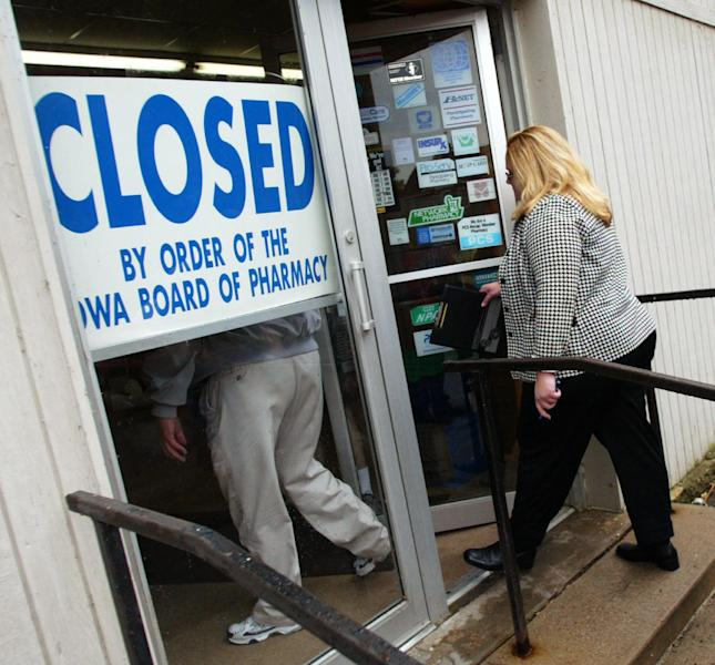 In this Sept. 12, 2003 photo, investigators enter the Union Family Pharmacy in Dubuque, Iowa, which was closed after authorities found evidence that it had illegally dispensed drugs on the Internet. On Aug. 9, 2012, a federal judge in Iowa dropped a 2007 indictment against fugitive Miami doctor Armando Angulo, charged in a scheme to sell prescription drugs and launder money, in part because of the size of the case file. The Drug Enforcement Administration says the evidence starts with the Dubuque raid that eventually secured the conviction of 26 defendants, including 19 doctors, in federal court in Iowa. The investigation dismantled two Internet pharmacies that illegally sold 30 million pills to customers. (AP Photo/Telegraph Herald, Dave Kettering)