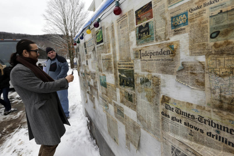 Sean Lennon stops to view news articles on display during a visit with Matthew and Tammy Manning, in Franklin Forks, Pa., Thursday, Jan. 17, 2013. Lennon and his mother, Yoko Ono, are on a bus tour of natural-gas drilling sites in northeastern Pennsylvania and visiting with residents who say they've been harmed by the controversial extraction process known as fracking. (AP Photo/Richard Drew)