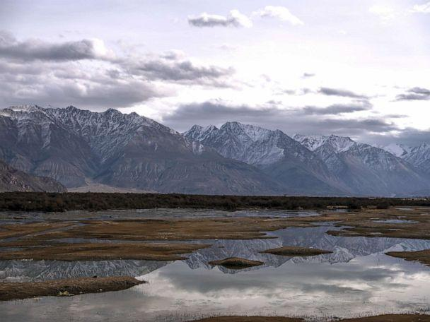PHOTO: Mountains are reflected in water where the Nubra river flows into the Shyok river as part of the Indus River system, that separates the Ladakh and Karakaoram ranges in Nubra, Jamma and Kashmir, India, Nov. 14, 2019. (Bloomberg via Getty Images, FILE)
