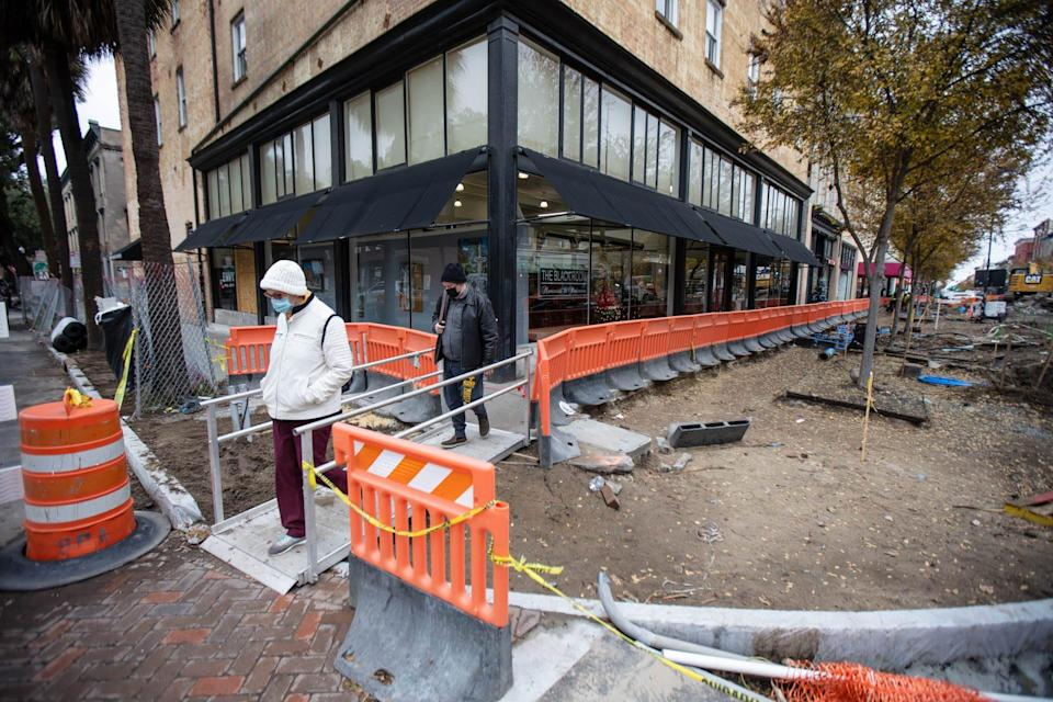Visitors use a temporary walkway near Envy Nail Bar as they make their way  through the construction for the Broughton streetscapes project.
