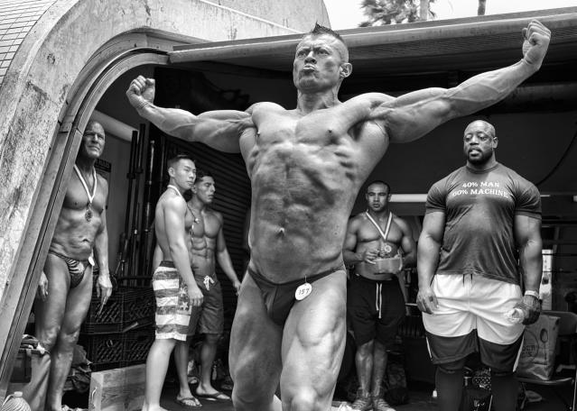 <p>A bodybuilder practices a pose backstage at the Mr. and Mrs. Muscle Beach Competition as a group of wary competitors watch him. Once the home gym of bodybuilders Arnold Schwarzenegger and Lou Ferrigno, the facility still serves the community as an iconic but accessible outdoor weight room. With a yearly membership cost of only $170 and aging gym equipment, the community gym has not yet succumbed to the gentrificationthat surrounds it. (© Dotan Saguy) </p>