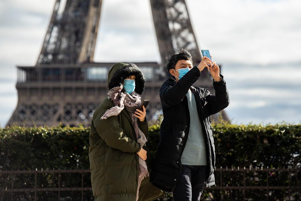 in Paris,in front of the eiffel tower,chinese tourists wear face mask to protect against the coronavirus ,with more and more people infected everyday ,and also in europe,chinese tourists wear protection mask, face mask against the contamination. A couple wearing a mask in the trocadero in front the eiffel tower (Photo by Jerome Gilles/NurPhoto via Getty Images)