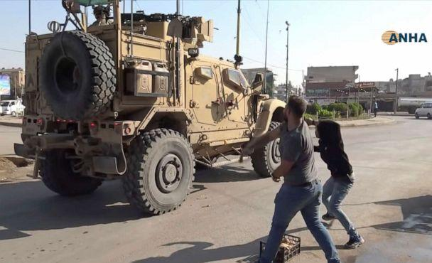 PHOTO: In this frame grab provided by Hawar News, ANHA, the Kurdish news agency, residents who are angry over the U.S. withdrawal from Syria hurl potatoes at American military vehicles in the town of Qamishli, northern Syria, Monday, Oct. 21, 2019. (ANHA via AP)