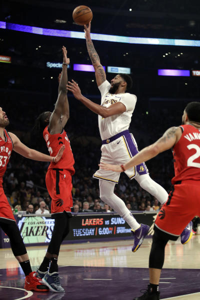 Los Angeles Lakers' Anthony Davis shoots over Toronto Raptors' Chris Boucher during the first half of an NBA basketball game Sunday, Nov. 10, 2019, in Los Angeles. (AP Photo/Marcio Jose Sanchez)