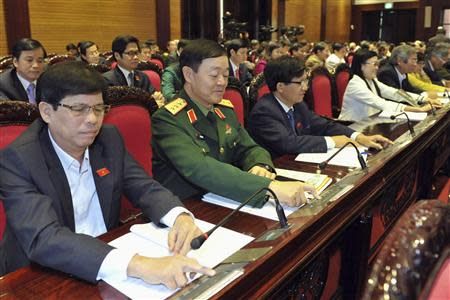 Vietnam's National Assembly's deputies press voting buttons to pass the new constitution during a meeting in Hanoi