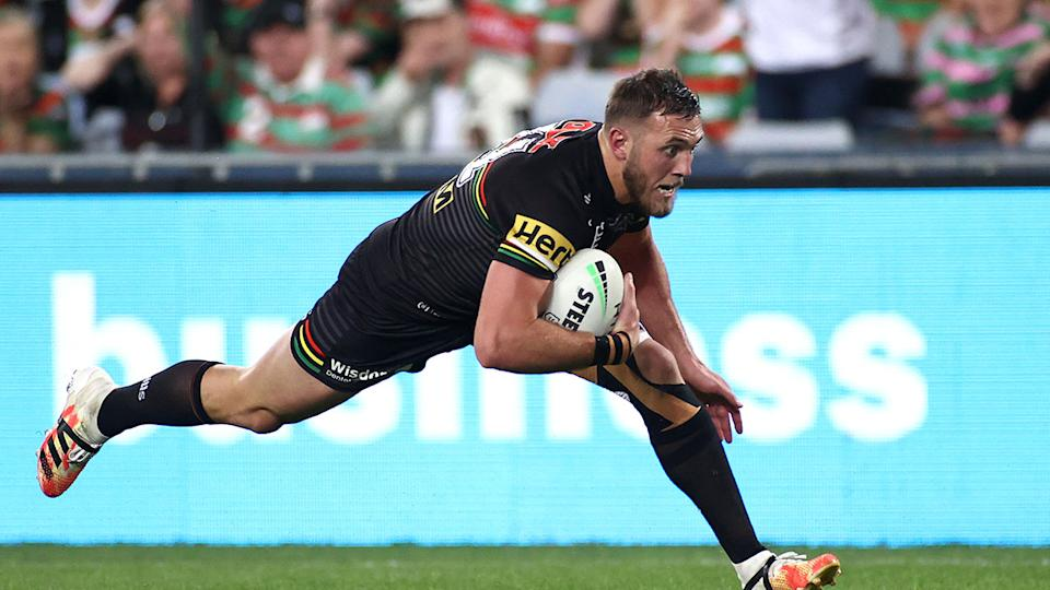 Pictured here, Kurt Capewell dives over for a try for the Penrith Panthers in the NRL.