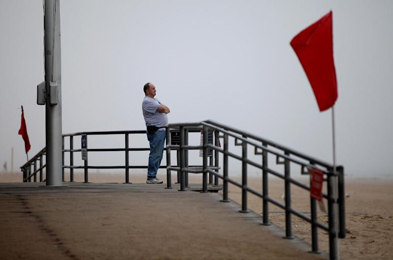 Thomas Walker, of Merrick, N.Y., who runs a business on the Coney Island boardwalk, looks out over the adjacent closed beach as he and others await the arrival of Hurricane Irene, Saturday, Aug. 27 2011, in the Coney Island section of  New York. (AP Photo/Craig Ruttle)