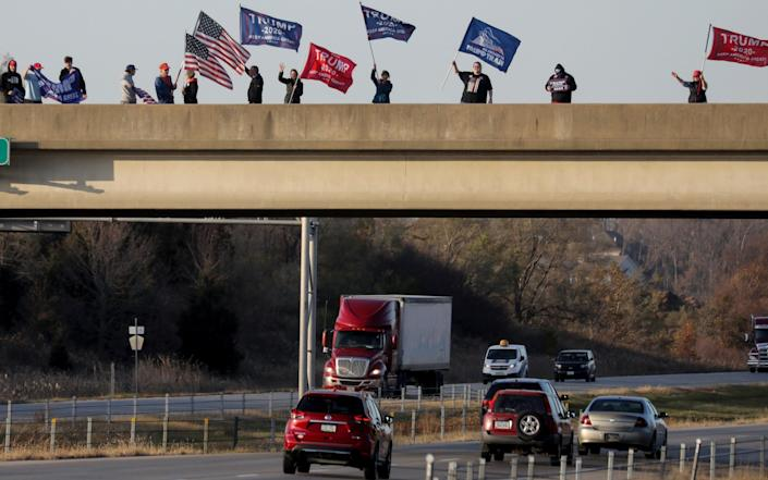 Supporters of President Donald Trump wave flags and banners from a highway overpass in Hiawatha, Iowa - Mario Tama /Getty Images North America