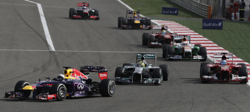 Red Bull driver Sebastian Vettel of Germany, left, leads Ferrari driver Fernando Alonso of Spain, right, and Mercedes driver Nico Rosberg of Germany, center, during the Formula One Grand Prix at the Formula One Bahrain International Circuit in Sakhir, Bahrain, Sunday, April 21, 2013. (AP Photo/Hassan Ammar)