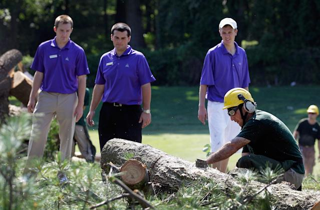 BETHESDA, MD - JUNE 30: Workers cut up a tree along the 14th fairway from overnight storm damage that delayed the start of Round Three of the AT&T National at Congressional Country Club on June 30, 2012 in Bethesda, Maryland. (Photo by Rob Carr/Getty Images)