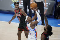Oklahoma City Thunder guard Shai Gilgeous-Alexander (2) shoots between Chicago Bulls forward Patrick Williams (9) and guard Coby White, right, during the second half of an NBA basketball game Friday, Jan. 15, 2021, in Oklahoma City. (AP Photo/Sue Ogrocki)