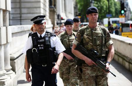 Soldiers walk with a police officer on Whitehall in London, Britain May 24, 2017. REUTERS/Neil Hall