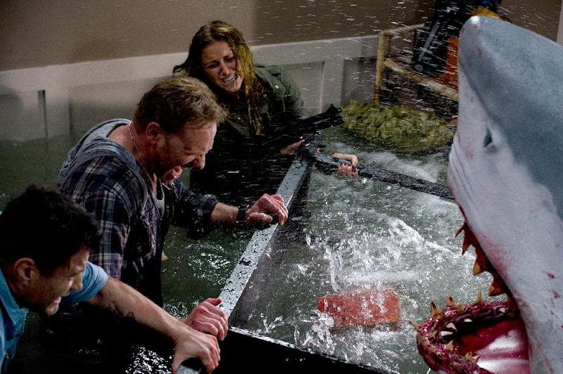 """In this image released by Syfy, Ian Ziering, second left, and Cassie Scerbo battle a shark in the Syfy original film """"Sharknado."""" The network is announcing a sequel to """"Sharknado,"""" which became an instant campy classic with its recent airing. The new film premieres in 2014. (AP Photo/Syfy)"""