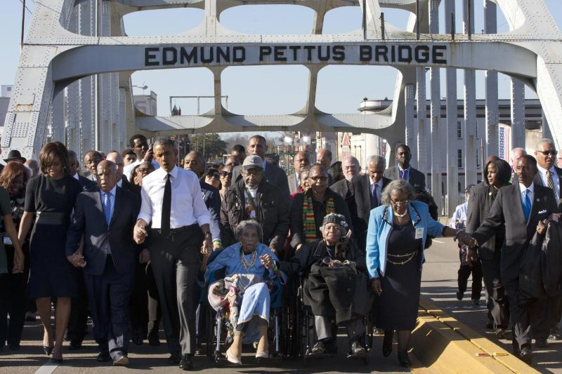 "President Barack Obama walks across the Edmund Pettus Bridge in Selma, Ala., with Amelia Boynton and Rep. John Lewis, who were beaten by police on ""Bloody Sunday. (Jacquelyn Martin, file/AP)"