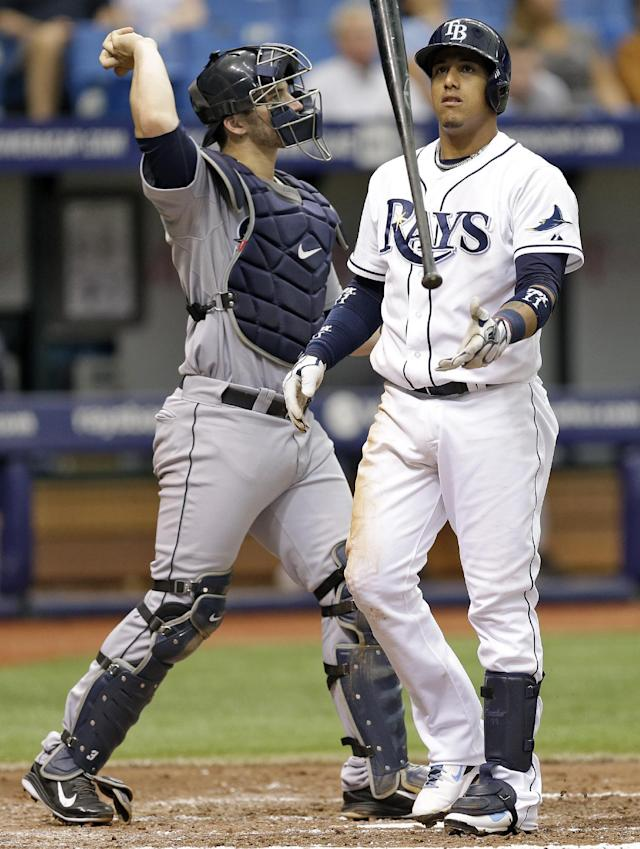 Tampa Bay Rays' Yunel Escobar, right, flips his bat as he strikes out against Seattle Mariners starting pitcher Erasmo Ramirez during the fourth inning of a baseball game Monday, June 9, 2014, in St. Petersburg, Fla. Catching for the Mariners is Mike Zunino. (AP Photo/Chris O'Meara)