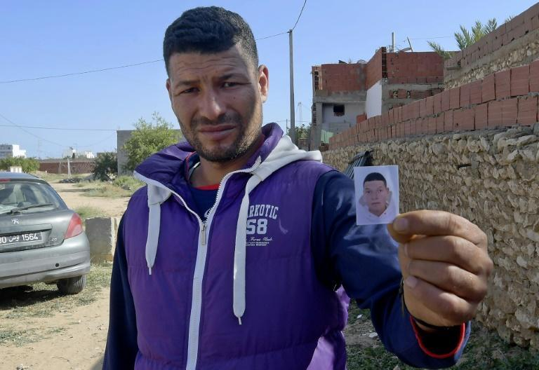 Yassin, the brother of the Nice assailant Brahim Issaoui, holds a passport picture of his sibling and says the family is struggling to believe he was responsible for the brutal killings