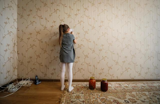 """Dana, 8, granddaughter of Petr Smotrich, a furnace operator at Aksu Ferroalloys Plant since 1978, draws as she plays in her grandfather's apartment in the town of Aksu, north-eastern Kazakhstan, February 22, 2018. REUTERS/Shamil Zhumatov SEARCH """"AKSU"""" FOR THIS STORY. SEARCH """"WIDER IMAGE"""" FOR ALL STORIES. TPX IMAGES OF THE DAY."""