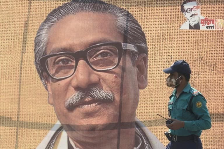 In this file photo taken on March 09, 2020 a policeman wearing a facemask amid fears of the spread of COVID-19 novel coronavirus, walks past a banner with a picture of Bangladesh's founder Sheikh Mujibur Rahman in Dhaka