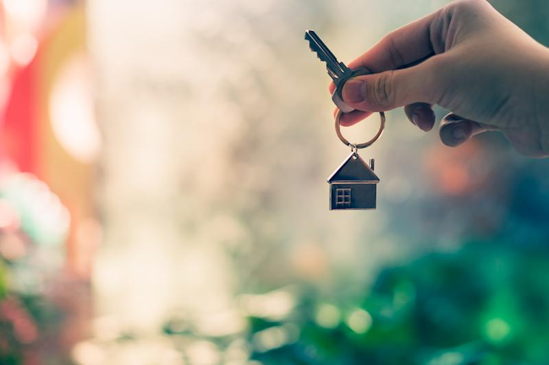 A person holds a key to a home in their hand.