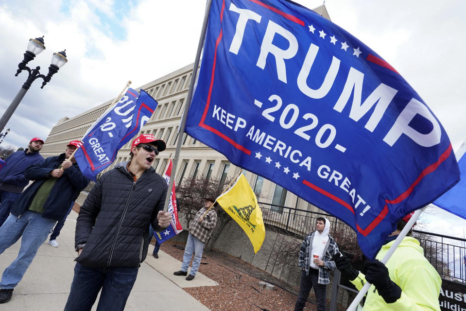 Max Versluys stands outside the Richard H. Austin state office building during a rally in Lansing, Mich., Saturday, Nov. 14, 2020. Michigan's elections board is meeting to certify the state's presidential election results. (AP Photo/Paul Sancya)