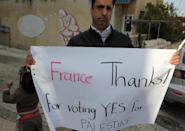 A Palestinian holds a poster as he thanks French lawmakers during a rally in the West Bank city of Ramallah, on December 2, 2014