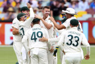 Australia's Josh Hazlewood, centre, is congratulated by teammates after dismissing India's Mayank Agarwal during play on day three of the fourth cricket test between India and Australia at the Gabba, Brisbane, Australia, Sunday, Jan. 17, 2021. (AP Photo/Tertius Pickard))