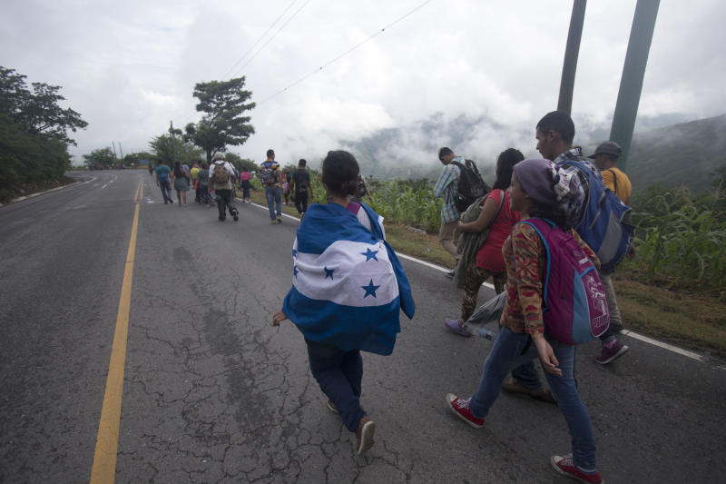 Honduran migrants bound for the U.S. border walk along a highway in Zacapa, Guatemala, Wednesday, Oct. 17, 2018. The group of some 2,000 Honduran migrants hit the road in Guatemala again Wednesday, hoping to reach the United States despite President Donald Trump's threat to cut off aid to Central American countries that don't stop them. (AP Photo/Moises Castillo)
