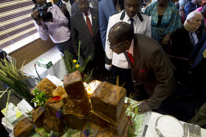 """Zimbabwe's President Robert Mugabe blows out the candles on his birthday cake as he marks his 93rd birthday at his offices in Harare, Tuesday, Feb. 21, 2017. Mugabe described his wife Grace, an increasingly political figure, as """"fireworks"""" in an interview marking his 93rd birthday. (AP Photo/Tsvangirayi Mukwazhi)"""