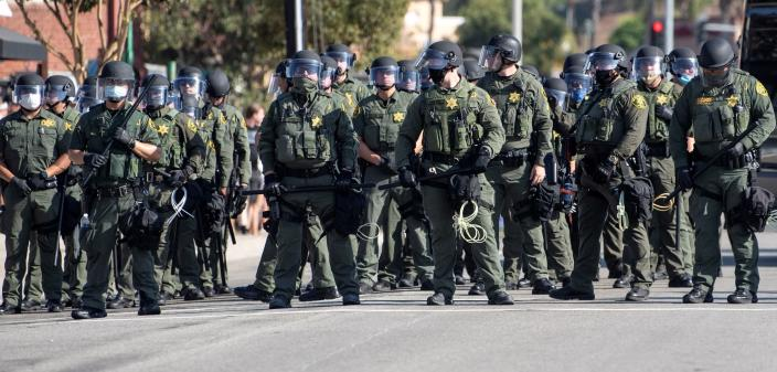 Orange County Sheriff deputies line up as Black Lives Matter protesters and counter protesters clash in Yorba Linda, Calif., Saturday, Sept. 26, 2020. Police eventually declared the event an unlawful gathering and cleared the streets near Yorba Linda and Imperial. Authorities said people were struck by a car and injured during the Black Lives Matter protest and counter protest about 30 miles southeast of Los Angeles. Orange County Sheriff's Department spokeswoman Carrie Braun says the injured were transported to a hospital with non-life-threatening injuries and the driver was detained. (Mindy Schauer/The Orange County Register via AP)