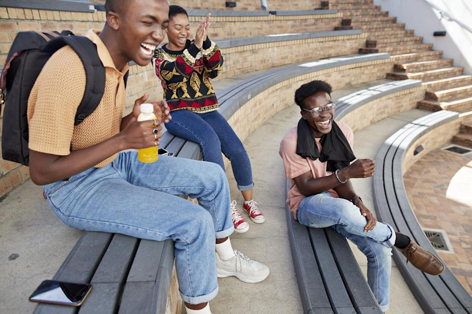 Cheerful young male and female friends enjoying on amphitheater steps at university campus