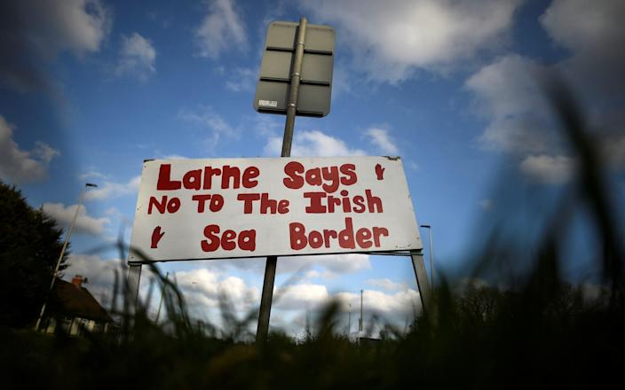 A sign with a message against the Brexit border checks in relation to the Northern Ireland protocol at the harbour in Larne - Clodagh Kilcyone/Reuters