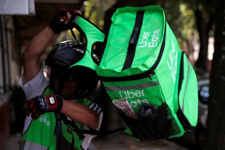 A man puts on a delivery bag with the logo of Uber Eats in Mexico City, Mexico May 20, 2019. REUTERS/Carlos Jasso