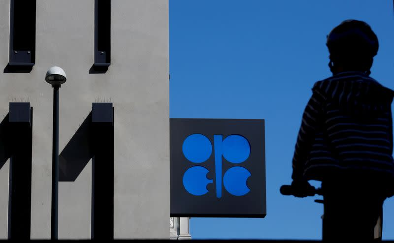 FILE PHOTO: A person passes the OPEC logo in front of its headquarters in Vienna