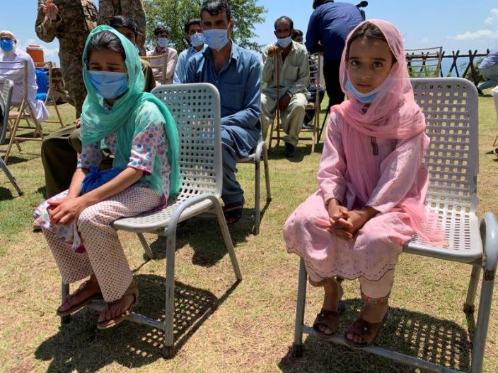 Sisters who got shrapnel wounds when a shell hit their family house, sit along with other villagers and journalists during a trip organised by the army, near the Line of Control (LoC) in Charikot Sector, Kashmir