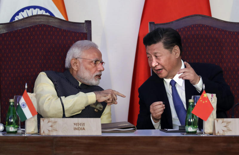 """FILE - In this Oct. 16, 2016, file photo, Indian Prime Minister Narendra Modi, left, talks with Chinese President Xi Jinping at the signing ceremony by foreign ministers during the BRICS summit in Goa, India. India's Ministry of External Affairs said Wednesday, Oct. 9, 2019, that Xi and Modi would meet for a second informal summit in the southern coast city of Chennai on Oct. 11 and 12 to """"exchange views on deepening"""" the two countries' development. (AP Photo/Manish Swarup, File)"""