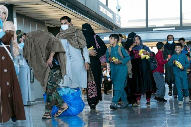 PHOTO: People evacuated from Kabul, Afghanistan, walk through the terminal before boarding a bus after they arrived at Washington Dulles International Airport, in Chantilly, Va., on Sept. 2, 2021. (Jose Luis Magana/AP)