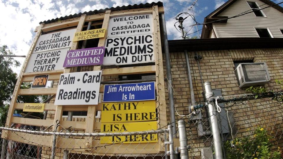 a side of a run down building with several signs advertising psychic mediums