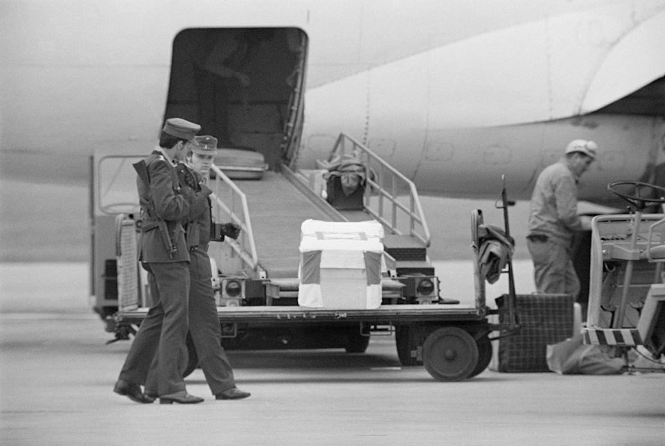 Caskets of murdered Olympians carried onto a plane