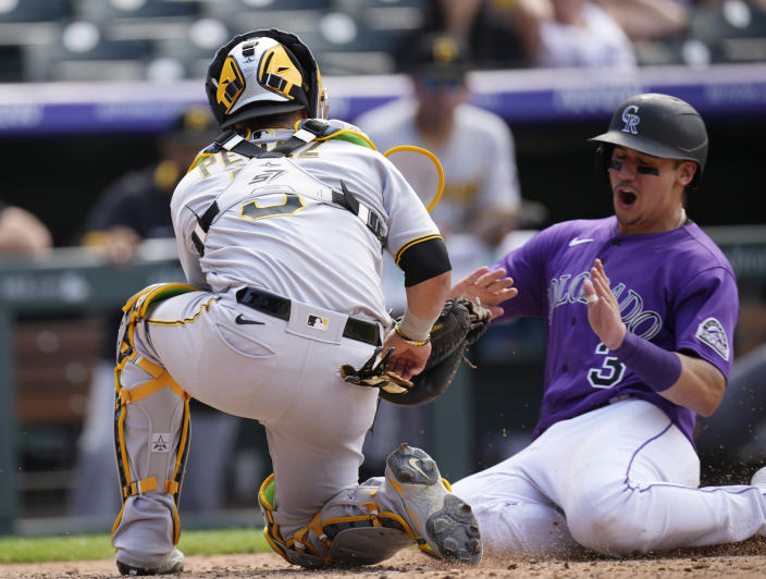 Pittsburgh Pirates catcher Michael Perez, left, tags out Colorado Rockies' Dom Nunez to end the seventh inning of a baseball game Wednesday, June 30, 2021, in Denver. (AP Photo/David Zalubowski)