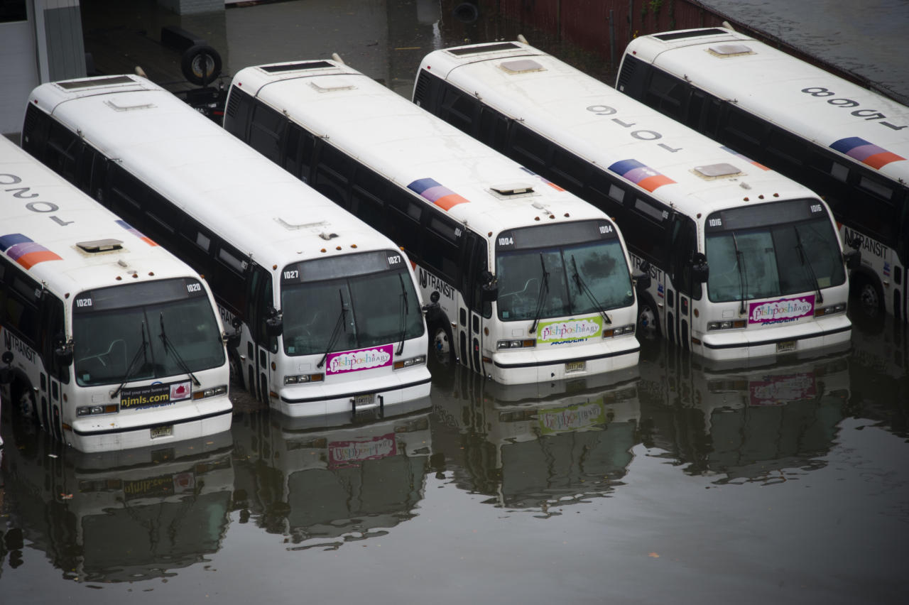 CORRECTS YELLOW CABS TO BUSES - A parking lot full of buses is flooded as a result of superstorm Sandy on Tuesday, Oct. 30, 2012 in Hoboken, NJ. (AP Photo/Charles Sykes)