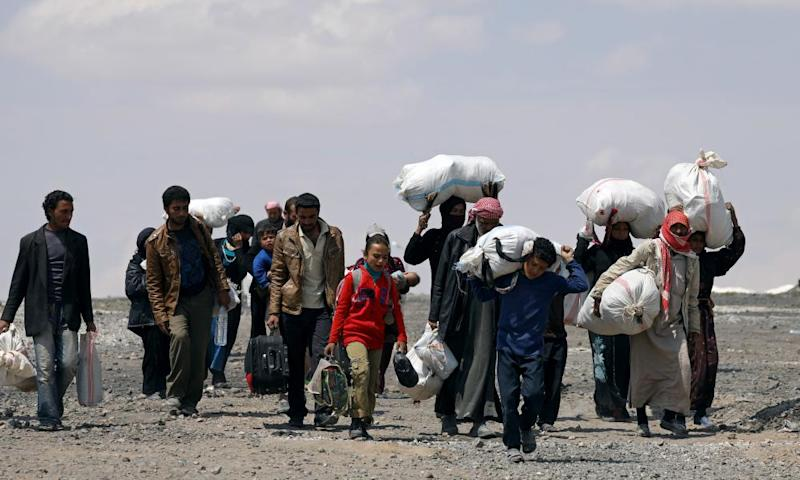 Syrians forced to flee Raqqa city carry their belongings as they leave a camp in Ain Issa
